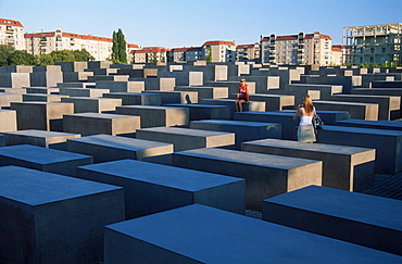 Holocaust Memorial to the Murdered Jews of Europe, field of stelae designed by architect Peter Eisenman in front tower blocks, Berlin, Germany