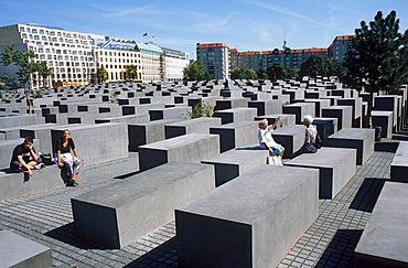 Tourists at Holocaust Memorial to the Murdered Jews of Europe, field of stelae designed by architect Peter Eisenman in front tower blocks, Berlin, Germany