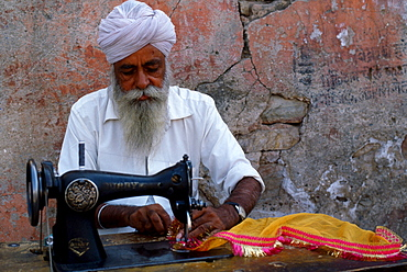 Indian man with turban sewing textiles, Udaipur, Rajasthan, India