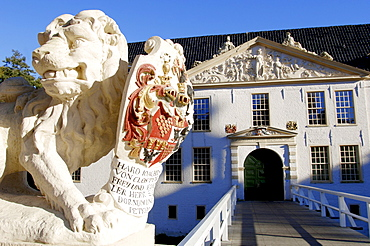 Lion sculpture and moated castle Norderburg, Dornum, Lower Saxony, Germany