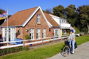 Bicyclist and house near Leer, Lower Saxony, Germany