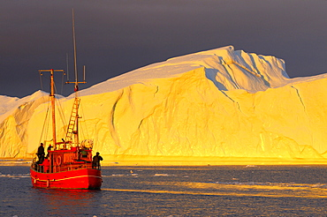 Fishing cutter as tourist boat, in front of iceberg, mouth Kangia Icefjord, Disko Bay, Ilulissat, West coast, Greenland / Jakobshavn