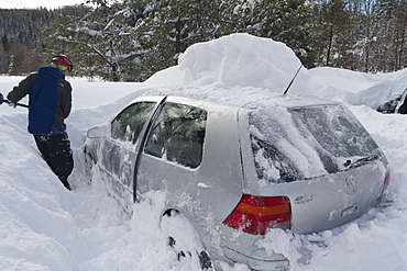 Man removing snow from car Gaspesie national park, Quebec, Canada
