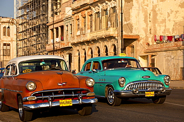 vintage US cars from the 50's and coulourful buildings in Centro Habana, Havana, Cuba, Caribbean