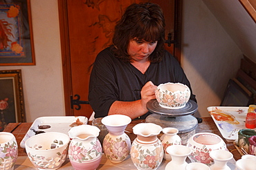Woman painting ceramics in pottery shop, Moulin Huet, Guernsey, Channel Islands, Great Britain / vases