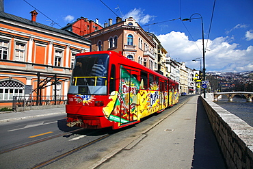 Red and yellow tram on bank of Miljacka River and Latin Bridge, Sarajevo, Bosnia and Herzegovina, Europe