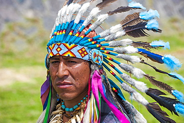 Indigenous man wearing a feather headdress, Quito, Pichincha Province, Ecuador, South America