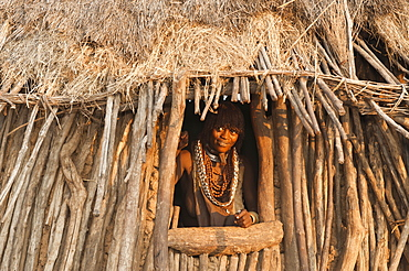 Pregnant Hamar woman with necklaces made of cowry shells coming out of her wooden hut, Omo River Valley, Southern Ethiopia, Africa