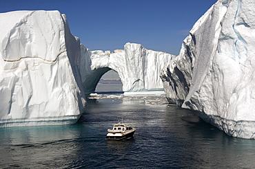 Icebergs in Disko Bay, natural arch and motorboat, UNESCO World Heritage Site, Ilulissat (Jakobshavn), Greenland, Denmark, Polar Regions