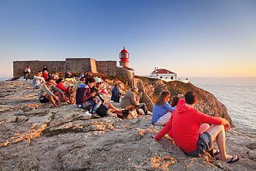 Tourists enjoying sunset at the lighthouse at Cabo de Sao Vicente, Sagres, Algarve, Portugal, Europe