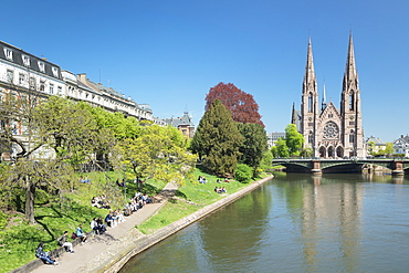People relaxing by the Ill River, and St. Paul's Church, Strasbourg, Alsace, France, Europe