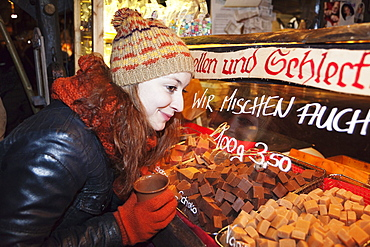 Young woman at the christmas fair looking at confection, Esslingen am Neckar, Baden Wurttemberg, Germany