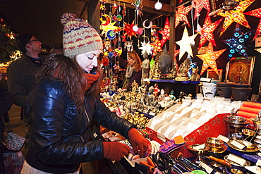 Young woman at the Christmas fair looking at Christmas decoration, Esslingen am Neckar, Baden Wurttemberg, Germany, Europe
