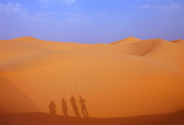 Tourists climbing up a sand dune in the Sahara Desert, Morocco