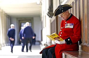 A Chelsea pensioner sitting outside the Royal Hospital Chelsea, London