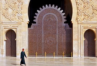 Man walking outside Hassan II Mosque in Casablanca, Morocco