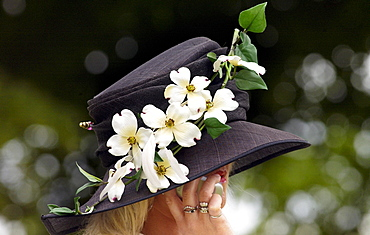 Race-goer wearing a hat with flowers in typical Ascot fashion at Royal Ascot Races. She is taking a call on her mobile cell phone.