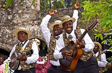 Muscians, playing guitar, banjo and maracas, in reggae style at cultural display in Montego Bay, Jamaica