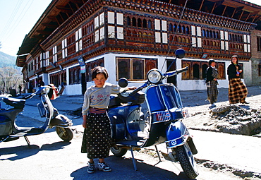 Girl standing by a  scooter, Paro, Bhutan