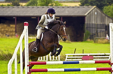Young woman rides a bay horse in an eventing competition, Gloucestershire, United Kingdom