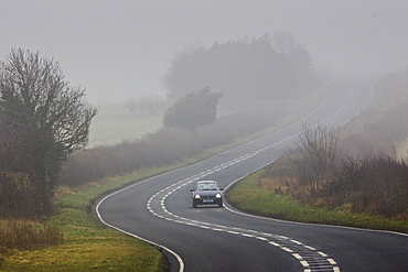 Car drives along foggy road, Oxfordshire,  United Kingdom
