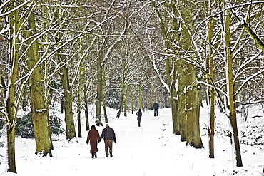 Couple walk hand in hand  across snow-covered Hampstead Heath, North London, United Kingdom