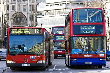 Public transport buses travel in heavy traffic in Trafalgar Square, London city centre, England, United Kingdom