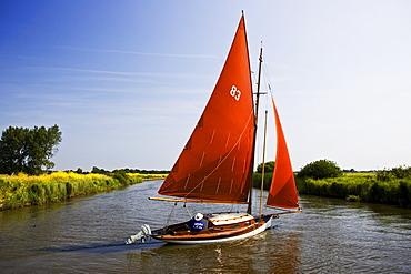 WORK LESS message on sailer's sweatshirt, sailing boat on Norfolk Broads, United Kingdom