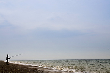 Man fishing on Cley Beach, Norfolk, United Kingdom