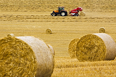 Tractor pulls a round baler to create straw bales, Cotswolds, United Kingdom