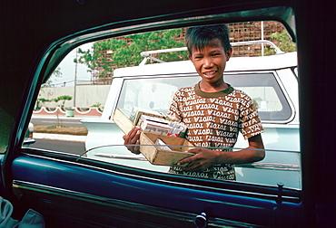Boy sells cigarettes at car windows in Manila, Philippines