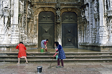 Women cleaning the steps outside a church in Lisbon, Portugal.