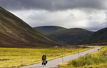 Cyclist on road through the Glen Clunie hills and Grampian Mountains, Scotland, United Kingdom