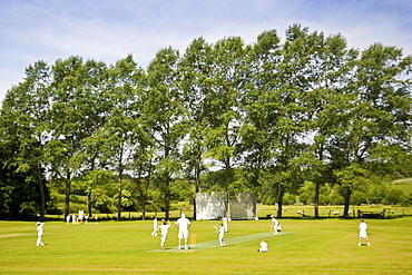 Children play cricket on village pitch, Swinbrook, The Cotswolds, England, United Kingdom