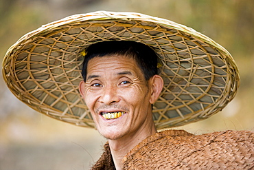 Fisherman in traditional coolie hat by the Li River, Guilin, China