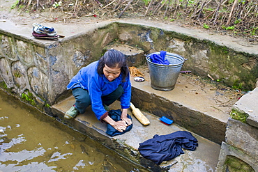 Woman washes her clothes in a stream by the road in Fuli Old Town, Xingping, China