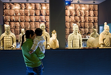 Tourists view Terracotta warriors on display in the Shaanxi History Museum, Xian, China