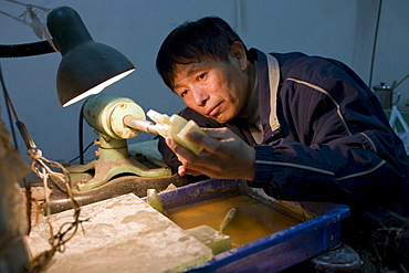 Jade craftsman at work in the Huahui Jade Factory and Showroom, Xian, China