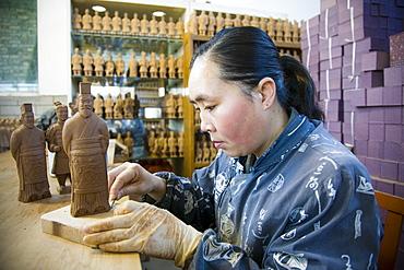 Woman makes Terracotta Warrior souvenirs in factory, Xian, China