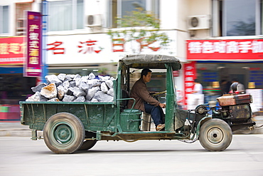 Man drives delivery tractor containing pile of construction stones in Yangshuo street, China