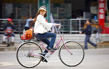 Young woman on a bicycle in Yangshuo street, China
