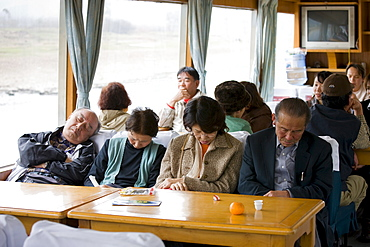 Tourists sleep as they travel by boat along Li River between Guilin and Yangshuo, China