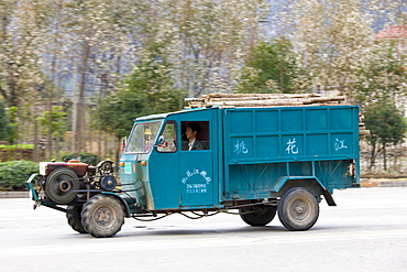 Delivery tractor truck containing pile of wood in Guilin, China. China's construction industry is thriving.