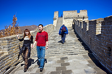 Tourist couple walk the ancient Great Wall of China at Mutianyu, north of Beijing, China