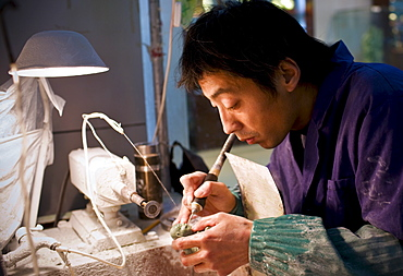 Jade craftsman at work in the Beijing Dragon Land factory in Beijing, China