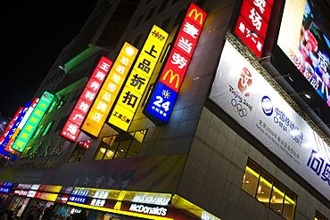 McDonalds fastfood restaurant with advertising alongside Chinese companies on Wangfujing Street, Beijing, China