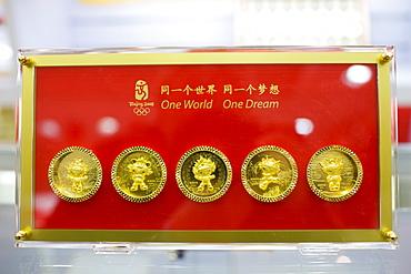 2008 Olympic Games Fuwa mascot characters medallion coins in souvenir shop, Wangfujing Street, Beijing, China