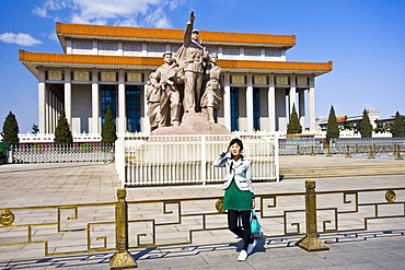 Tourist by statue elebrating the navy, army, airforce and workers, by Mao's Mausoleum, Tian'an Men Square, China