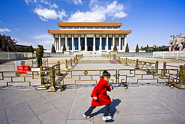 Young girl runs past a soldier outside Mao's Mausoleum, Tian'an Men Square, Beijing, China