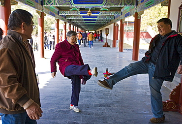 Pensioners play shuttlecock with their feet in the Ghost Corridor in park of the Temple of Heaven, Beijing, China